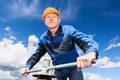 stock photo of valves  - Senior Caucasian worker in a hardhat at the factory with the pipe valve against blue sky - JPG