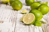 stock photo of mojito  - Fresh limes on wooden table - JPG