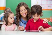 stock photo of classmates  - Children using digital tablet with teacher at classroom desk - JPG