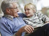stock photo of grandparent child  - Happy little girl with grandfather reading story book at home - JPG