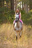 woman in pink dress riding horse through forest