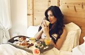 image of bed breakfast  - beautiful woman having breakfast in the hotel bed - JPG