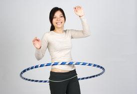 stock photo of hulahoop  - happy beautiful eurasian girl dooing hula hoop - JPG