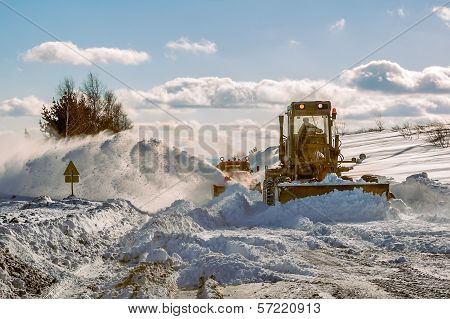 Grader cleaning road in winter