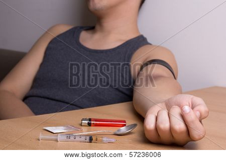 Drugs, Syringe, Spoon, Lighter And Stoned Male Addict