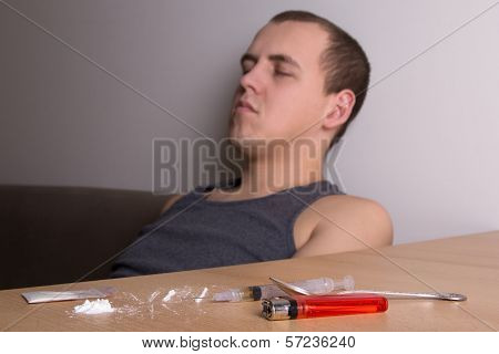 Addicted Man With Drugs On The Table
