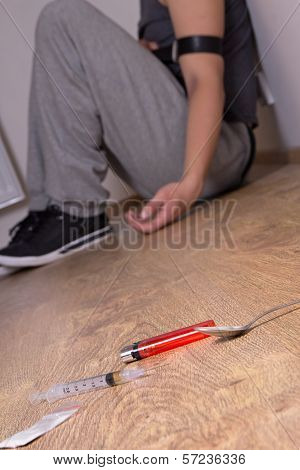 Drugs And Addict Sitting On The Floor