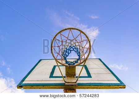 Basketball basket visible from the bottom on the blue sky in distance.