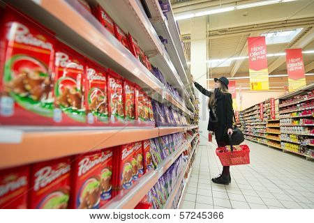 Young girl shopping chocolates in a supermarket
