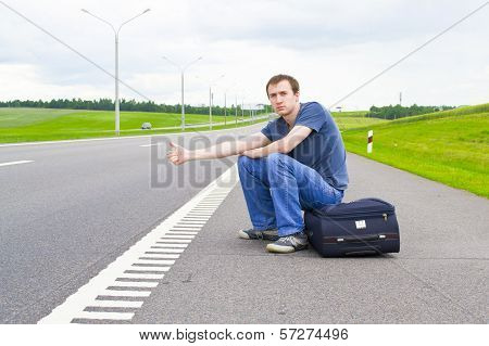 The young man pending on road with a suitcase