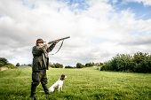 stock photo of hunters  - Hunter with dog aiming with his rifle