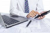 pic of calculator  - Portrait of a businessman checking financial data with calculator - JPG