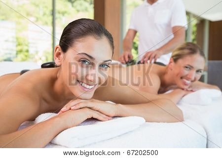 Pretty friends lying on massage tables with hot stones on their backs in the health spa