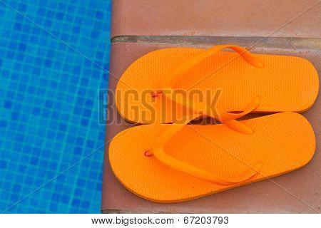 orange flip flops on pool edge