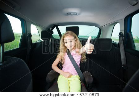Child in car. Happy girl wearing seatbelts