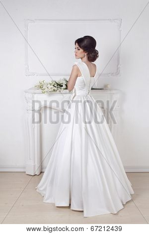 Beautiful Charming Bride In Wedding Luxurious Dress Posing Against A White Modern Wall