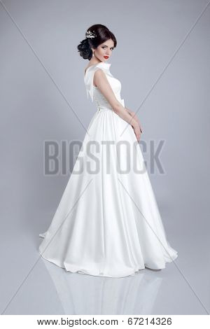 Fashionable Bride Model In Wedding Dress Isolated On Gray Background. Studio Photo