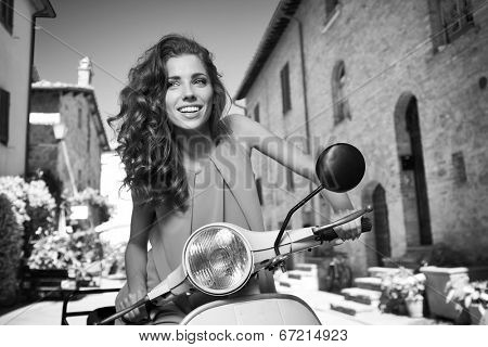 Italian woman on a scooter on the streets of the Tuscan town. BW shoot