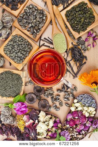 Tea glass cup and collection of different dry types tea (green,black, herbal) on kitchen wooden table background top view