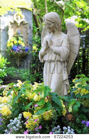Statue of a praying angel in the garden.