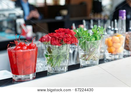 Cocktail cherries, herbs and flowers on bar counter