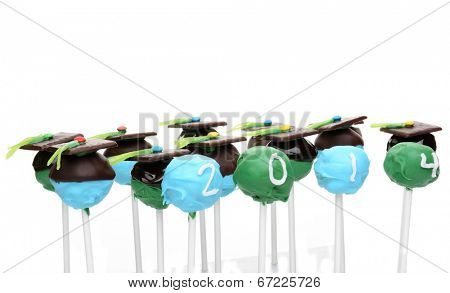 Closeup of a group of homemade cake pops decorated for Graduation. The cake pops ade decorated to have the look of a mortar board and four have the year 2014.