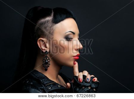 woman with modern unusual haircut with shaved sides, against dark studio background
