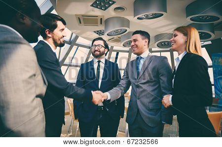 Group of business people looking at their colleagues handshaking after striking grand deal