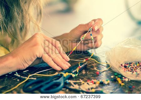 Woman making bracelet at home