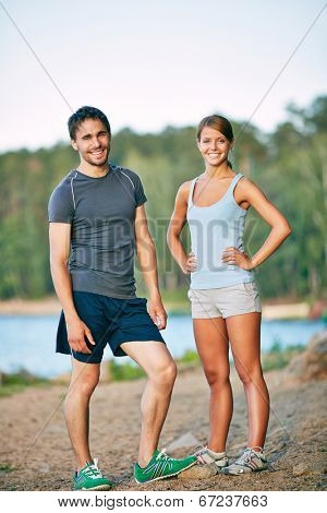 Photo of young sporty couple in activewear looking at camera outdoors