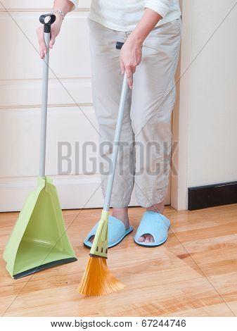 housewife cleaning floor by broom