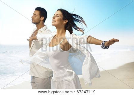 Young couple enjoying summer sun and wind on the beach. Pretending to fly eyes closed, arms wide open, smiling.