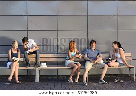College students sitting on bench by modern wall outside campus