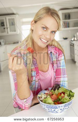Teenage girl eating salad