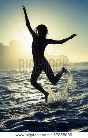 Happy blonde in the sea leaping in bikini on a sunny day