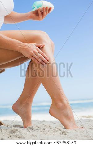 Woman rubbing sunblock on her leg at the beach on a sunny day