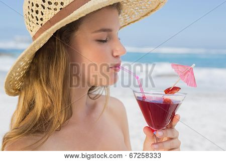 Pretty blonde sipping cocktail on the beach on a sunny day