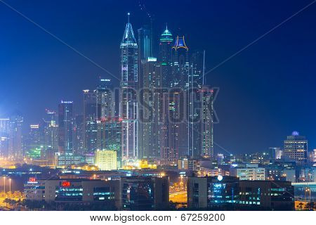 DUBAI, UAE - MARCH 30: Skyscrapers of Dubai Marina at night on March 30, 2014, UAE. Dubai Marina is a district in Dubai with artificial canal city who accommodates more than 120,000 people.