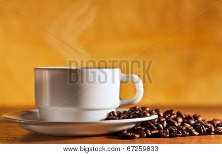 White Cup Of Hot Coffee With Steam Is On The Table