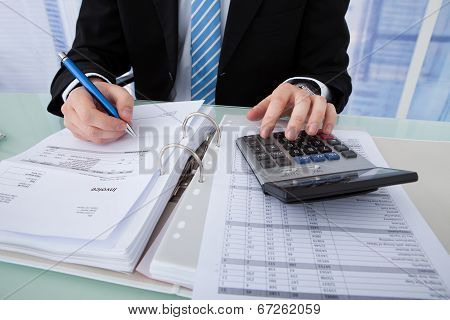 Businessman Calculating Invoice At Office Desk