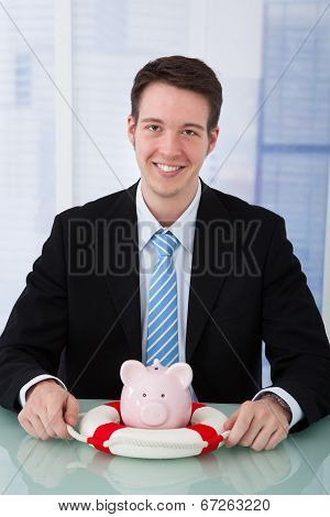 Businessman Protecting Piggybank With Lifebelt
