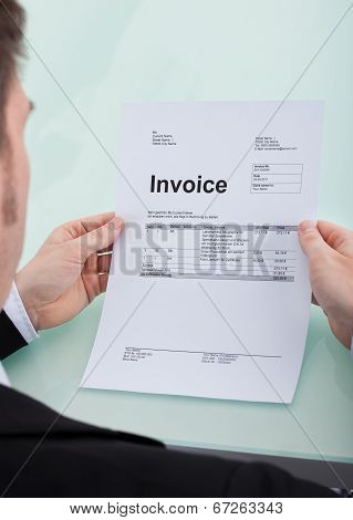 Businessman Reading Invoice At Desk