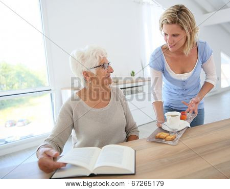 Home helper giving tea to elderly woman