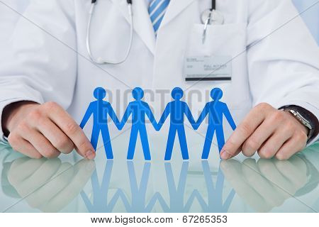 Doctor Holding Blue Paper People Chain At Desk