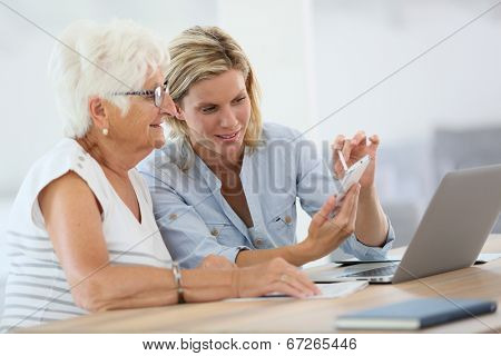 Homehelp with elderly woman using smartphone
