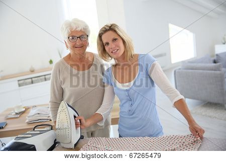 Portrait of senior woman with housekeeper