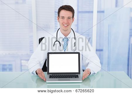 Doctor Presenting Laptop With Blank Screen At Desk