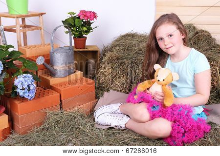 Beautiful small girl in petty skirt holding teddy bear on country style background