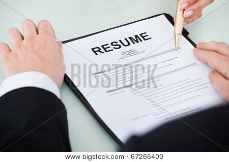 Businessman With Resume At Desk