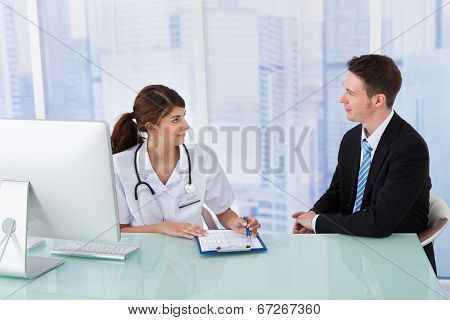 Doctor Showing Report To Businessman In Clinic